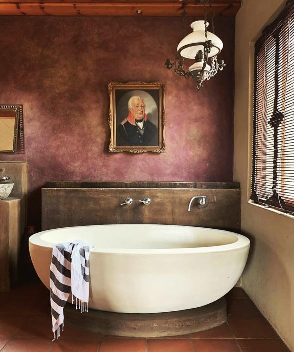 boondocks bathroom with old portrait and bath